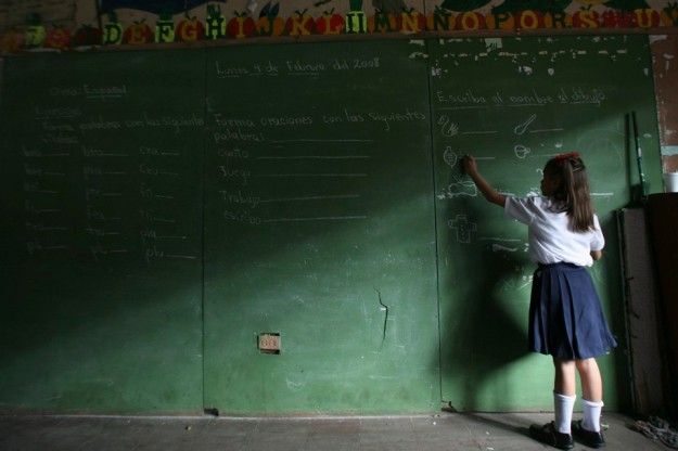 A girl writes on a chalk board during the opening of the elementary school year in the old center of Managua